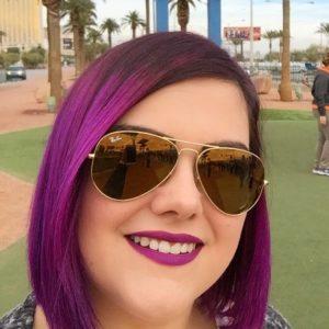 Porträtfoto von Jessica Hassler mit lila Haaren und gold verspiegelter Sonnenbrille, fotografiert vor dem Las Vegas Willkommensschild