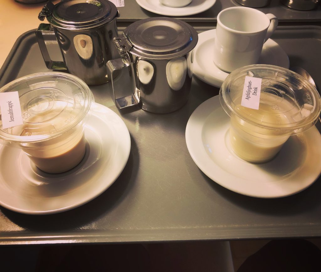 Tablett mit Milchkanne, Kaffeekanne, Malzgetränk und Joghurtgetränk im Krankenhaus.