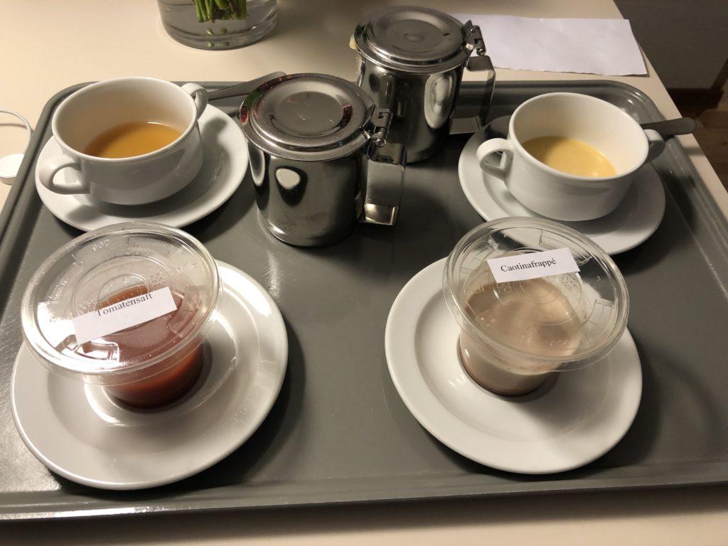 Tablett mit einer Schüssel Bouillon, Cremesuppe, Tomatensaft und Kakaogetränk im Krankenhaus.