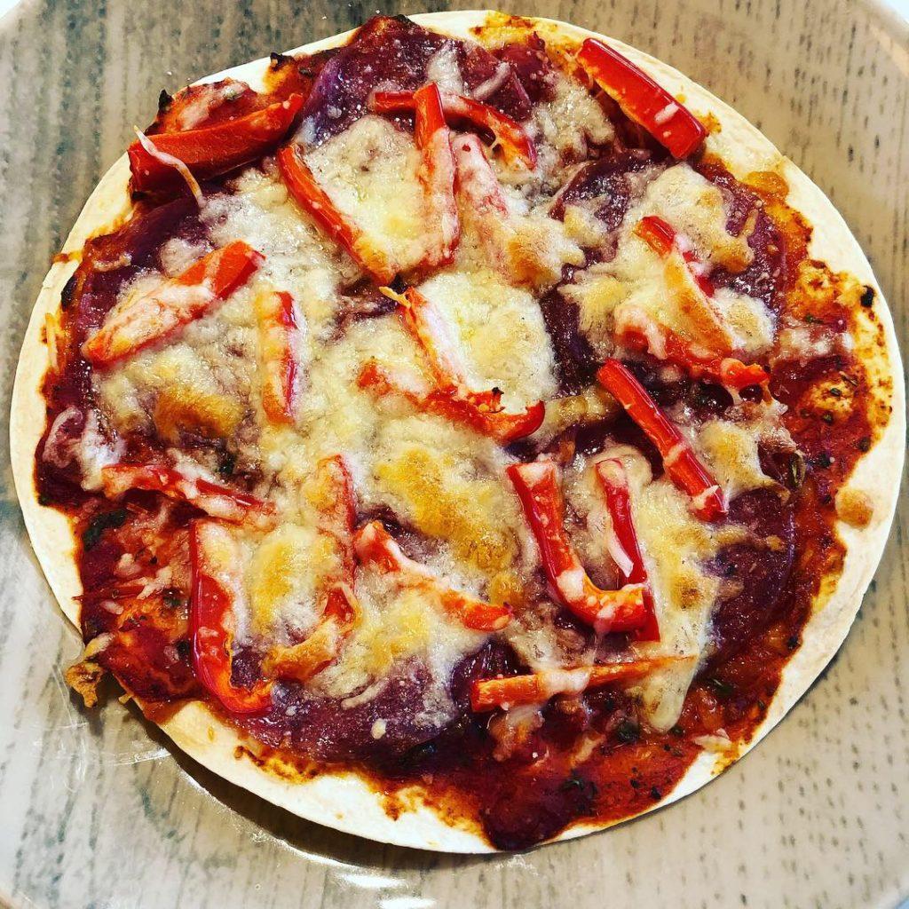Pizza aus einem Tortillafladen belegt mit Salami,Paprika und Käse