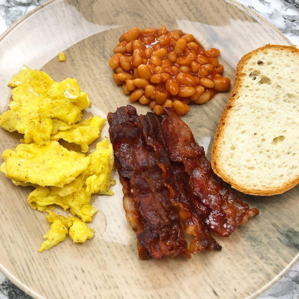 Bacon, Rührei und Baked Beans mit einer Scheibe Weissbrot