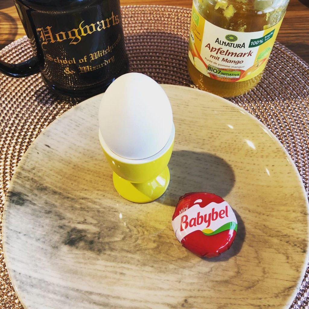 Frühstücks-Ei, Babybel auf einem Teller mit Kaffeetasse und Fruchtpüree