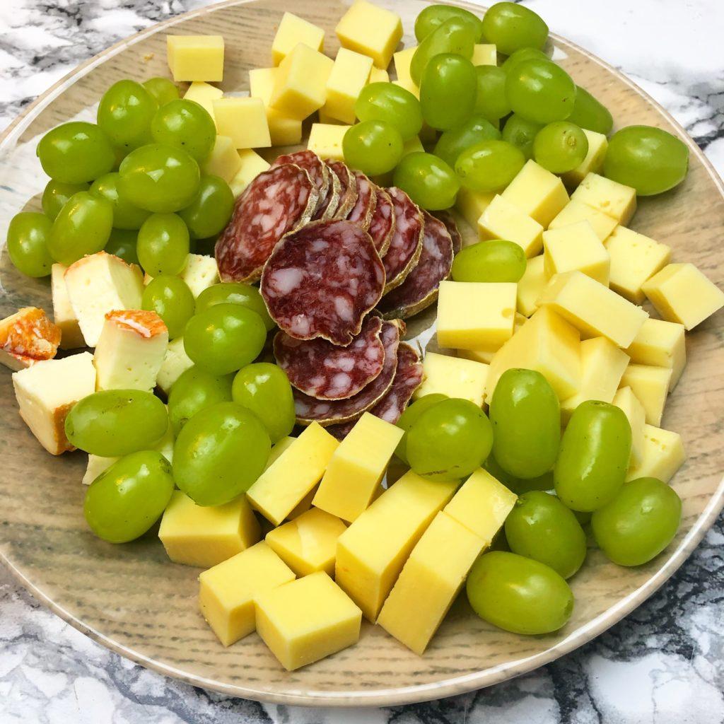 Verschiedene Käsewürfel mit Trauben und Salami auf einem Teller angerichtet