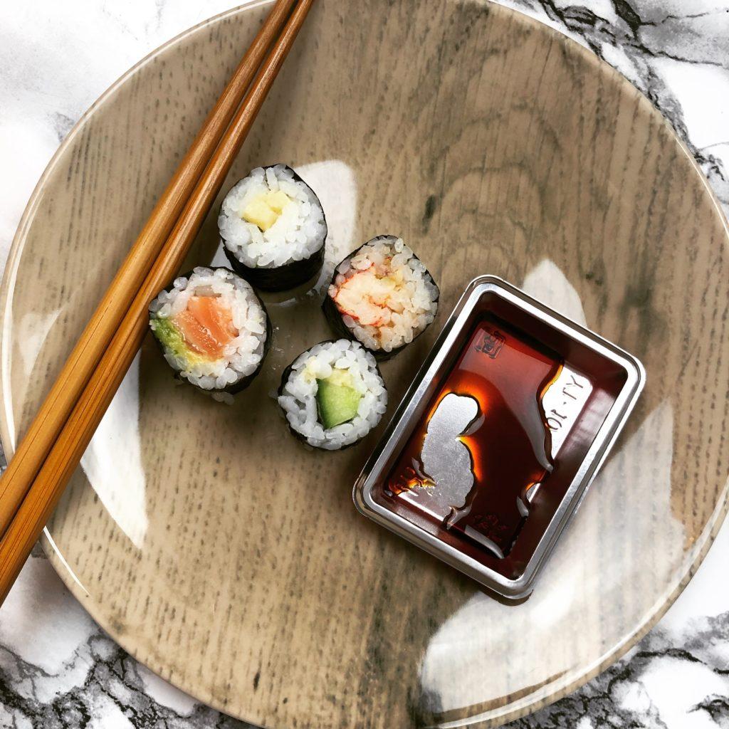 4 Rollen Sushi mit einer Schale Sojasauce und Essstäbchen
